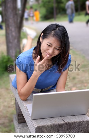Young beautiful Asian woman working outdoors angrily with her laptop - stock photo