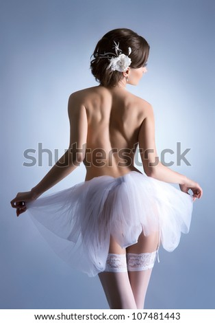 Young beautiful ballet dancer over blue background - stock photo