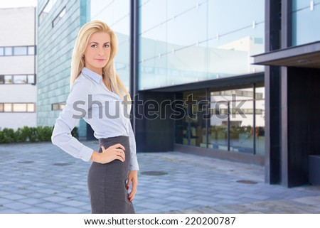 young beautiful blond business woman standing on street against office building - stock photo