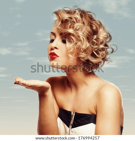 young beautiful blond Female blowing kissed to her valentine - stock photo
