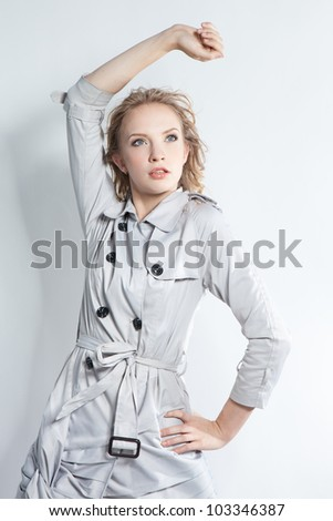 Young beautiful blond girl in a black man's jacket over dark background - stock photo