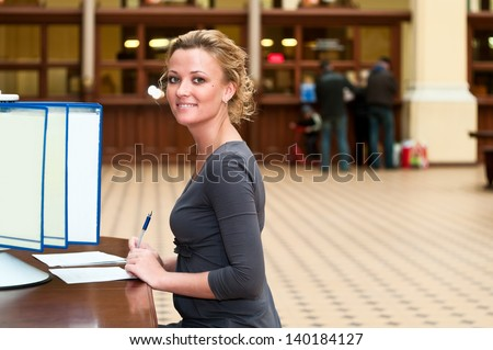 Young beautiful blond girl sitting at a table near the bar with the information and looks for - stock photo