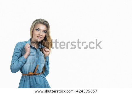 Young beautiful blond lady smiling in jeans dress, holding collar of a denim blouse. Studio portrait isolated on white of a young attractive hipster lady wearing jeans suit, fashion beauty summer - stock photo
