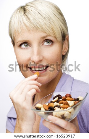 young beautiful blond woman eating nuts close up - stock photo