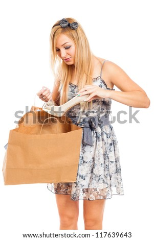 Young beautiful blond woman holding shoe and shopping bag, isolated on white background. - stock photo