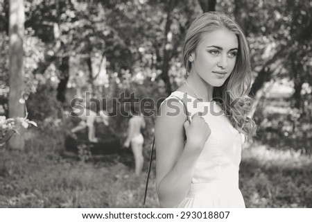 Young beautiful blond woman in summer nature background, black and white portrait - stock photo