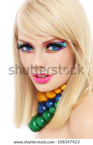 Young beautiful  blond woman with fancy make-up and colorful wooden necklaces - stock photo