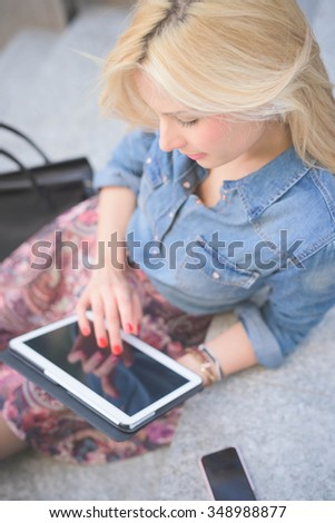 Young beautiful blonde caucasian girl seated on a staircase using a tablet looking downward the screen - communication, technology, social network concept - stock photo