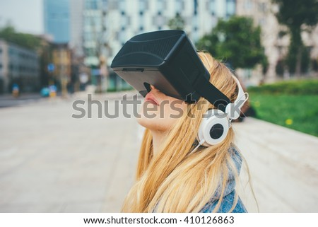 Young beautiful blonde caucasian woman sitting using 3D viewer looking up - futuristic, multitasking, technology concept - stock photo