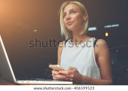 Young beautiful blonde female holding mobile phone while sitting with portable net-book in coffee shop interior, charming dreamy woman using cell telephone and laptop computer during rest in cafe  - stock photo