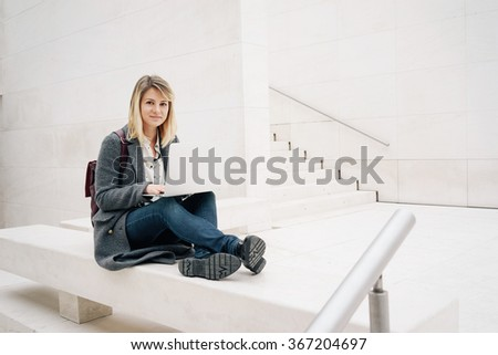 young beautiful blonde female student learning on-line on her laptop computer while sitting on the stone bench.copy space area for your text message or content - stock photo