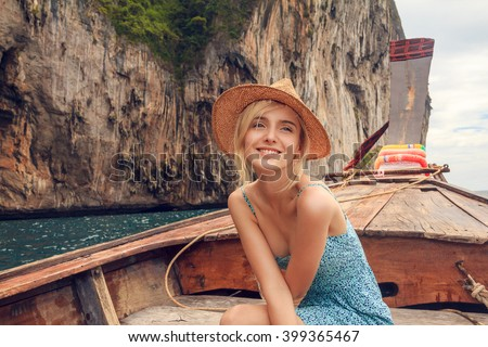 Young beautiful blonde girl cruising on retro wood boat by Andaman sea and behind her you can see Ko Phi Phi Lee Island i full glory. Dressed in beautiful blue dress and wearing straw hat. - stock photo