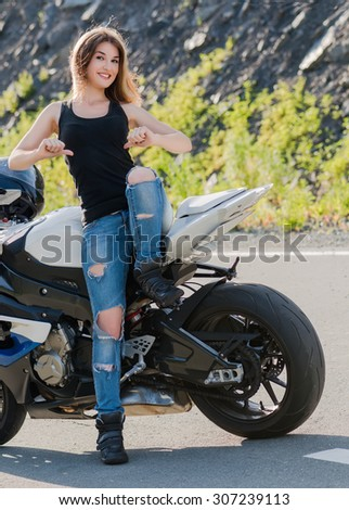 Young beautiful blonde girl in trendy jeans and black t-shirt is pointing on place where it can be your image. She is standing near modern motorcycle. Outdoor portrait in soft sunny colors. - stock photo