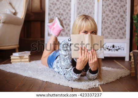 Young beautiful blonde girl lying on the floor on a carpet - stock photo