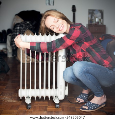 Young beautiful blonde girl sitting near heater radiator and hugs.  - stock photo