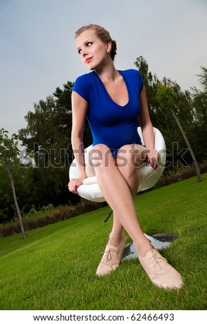Young beautiful blonde girl sitting on a swivel chair in a garden - stock photo