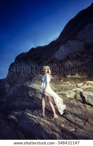 Young beautiful blonde girl wearing white dress walking on cliffs after sunset. - stock photo