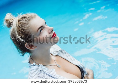 young beautiful blonde girl with a good figure in a white shirt with red lips make-up posing in a pool of blue water . outdoor portrait close up.   - stock photo