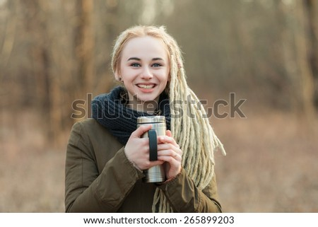 Young beautiful blonde hipster woman in scarf and parka with dreadlocks hairstyle posing on a blurry forest background with thermos cup - stock photo
