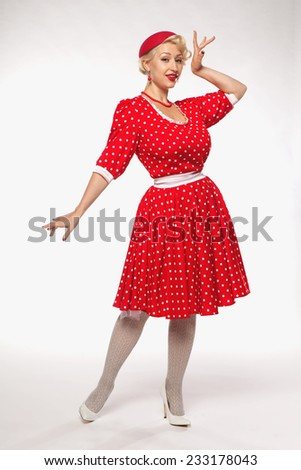 young beautiful blonde in red dress pin-up in the studio - stock photo