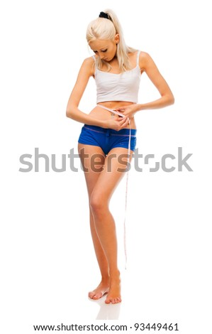 Young beautiful blonde is measuring her waist - stock photo