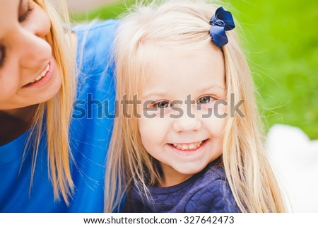 Young beautiful blonde mother and her cute little daughter smiling and relaxing in park in summer. Both wear blue dresses. Small bow in daughter hair. Little lady smiling happily and so do mom - stock photo