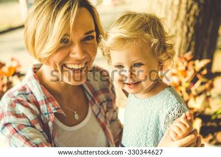 Young beautiful blonde mother with her little daughter. Toned image - stock photo