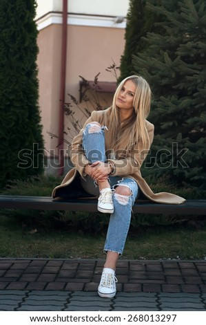 Young beautiful blonde sitting on the bench - stock photo
