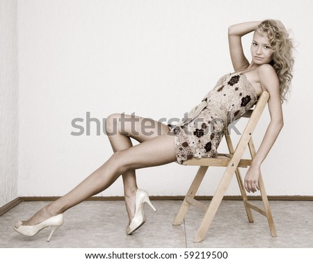 young beautiful blonde sitting on wooden chair - stock photo