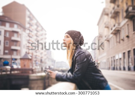 young beautiful blonde straight hair woman in the city with headphones listening to music - relax technology concepts - stock photo
