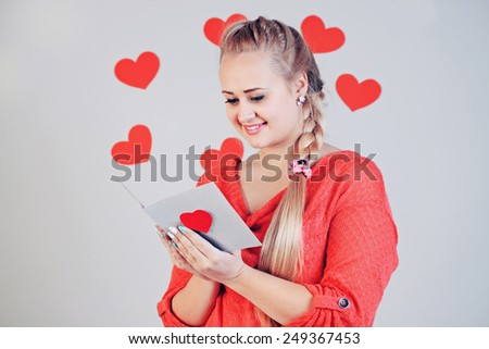 young beautiful blonde woman holding a card with heart - stock photo