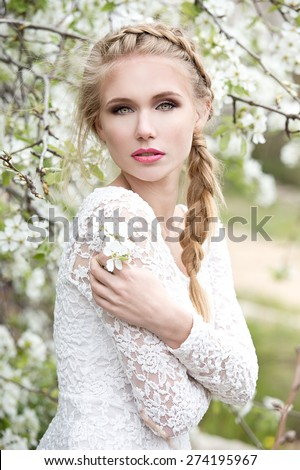 Young beautiful blonde woman in blooming garden. Bride. - stock photo