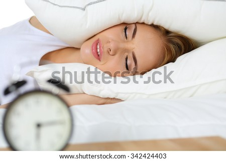 Young beautiful blonde woman lying in bed suffering from alarm clock sound covering head and ears with pillow making unpleasant face. Early wake up, not getting enough sleep, going work concept - stock photo