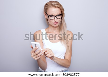 Young beautiful blonde woman texting by mobile phone. Attractive angry girl. Grey wall. - stock photo