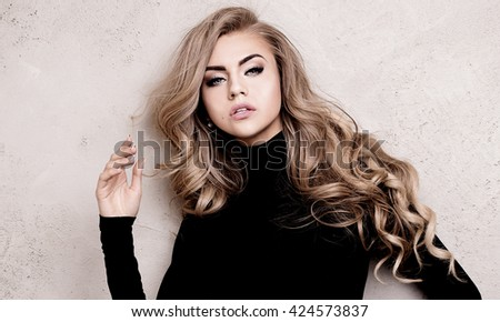 Young beautiful blonde woman wearing black sexy clothes posing in studio, looking at camera. Glamour makeup. Long healthy hair.  - stock photo