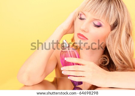 Young beautiful blonde  woman with bottle of perfume  on yellow background - stock photo