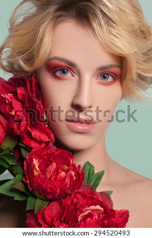 young beautiful blonde woman with red makeup and flowers on green background. studio shot. looking at camera. Developed from RAW, edited with special care and attention - stock photo