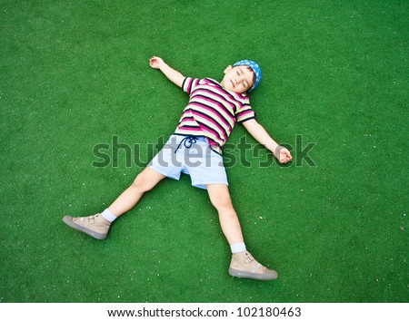 Young beautiful boy laying on plastic green grass pretending sleep in starlike pose - stock photo