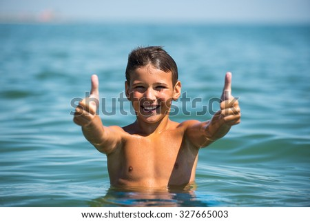 Young beautiful boy showing thumb up sign. - stock photo