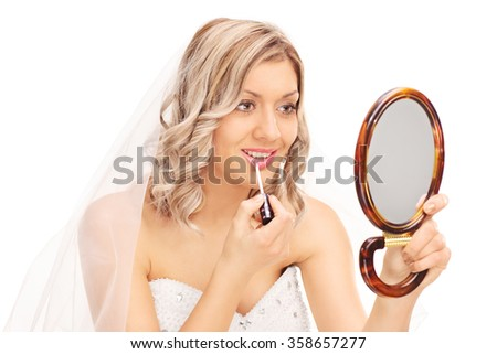 Young beautiful bride applying make-up and looking in a mirror isolated on white background - stock photo