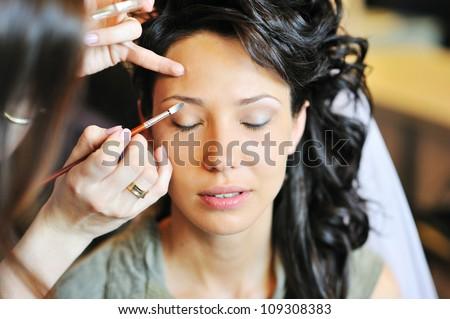 Young beautiful bride preparing