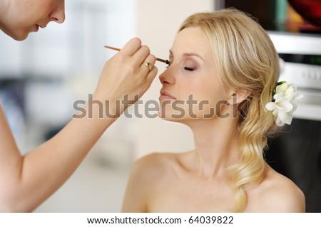 Young beautiful bride applying wedding make-up  by professional make-up artist - stock photo
