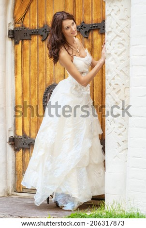 Young beautiful bride in white wedding dress standing about vintage wooden doors. - stock photo