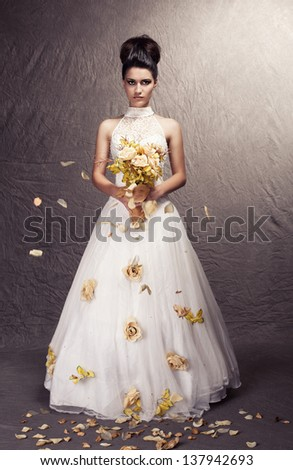 young beautiful bride posing on grunge background with leaves on the floor - stock photo