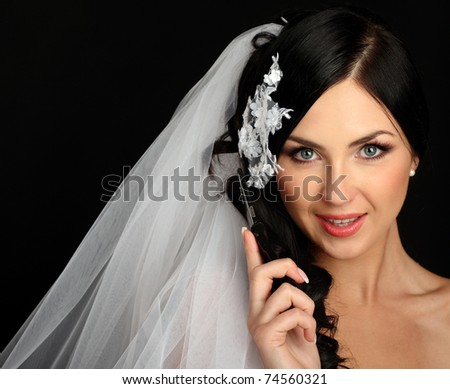 Young beautiful bride talking on mobile phone, isolated on black, studio shot - stock photo