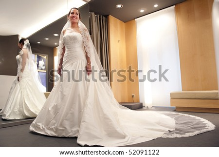 Young beautiful bride trying her dress in shop - stock photo