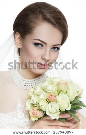 Young beautiful bride with stylish make-up and hairdo holding bouquet over white background - stock photo