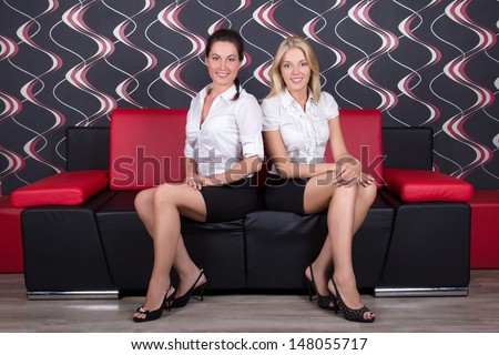 young beautiful brunette and blond sitting on the sofa - stock photo