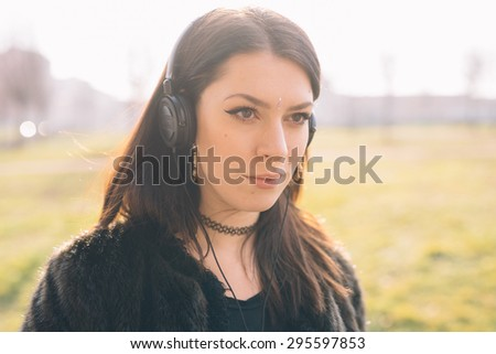 Young beautiful brunette caucasian girl listening to the music with headphones in a city park - music, relax, serenity concept - stock photo