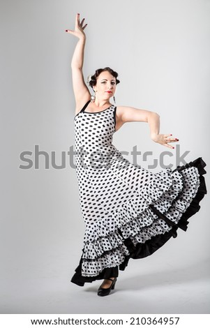 young beautiful brunette female spanish flamenco dancer in black and white flamenco dress dancing with her arms in studio on gray background - stock photo